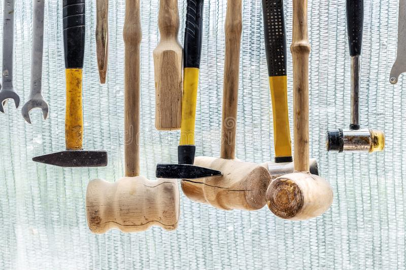 Set of different purpose hammers and tools hanged on wall against plastic window in craftsman carpentry workshop. DIY concept royalty free stock photo