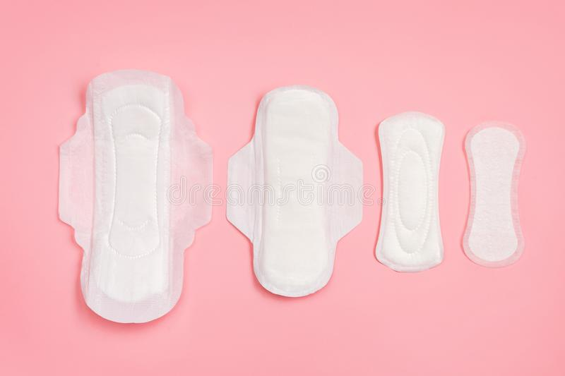 Set of different sanitary napkins on pink background. Concept of critical days, menstruation royalty free stock image