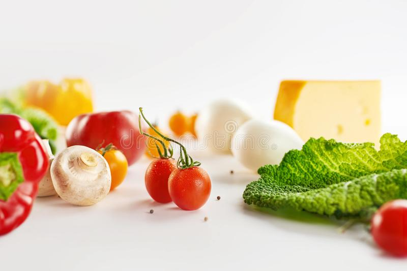Set of different seasonal vegetables on a light gray background. Cherry Tomato, Mushrooms. Peppers, Greens royalty free stock photography
