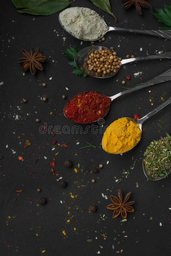 Set of various spices and herbs on black slate background royalty free stock photos