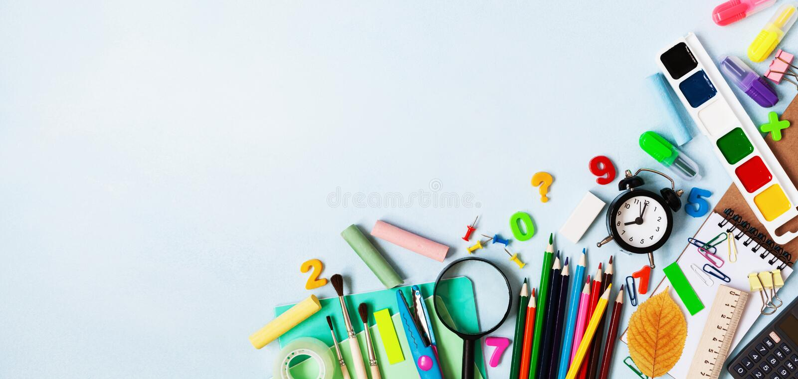 Set of different stationery, alarm clock and colorful supplies on blue background. Back to school concept. Banner format. Top view stock images