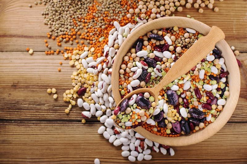 Vegan protein source. Legumes - lentils, chickpeas, beans, green mung bean, seeds and nuts on wooden background. Top view stock photo