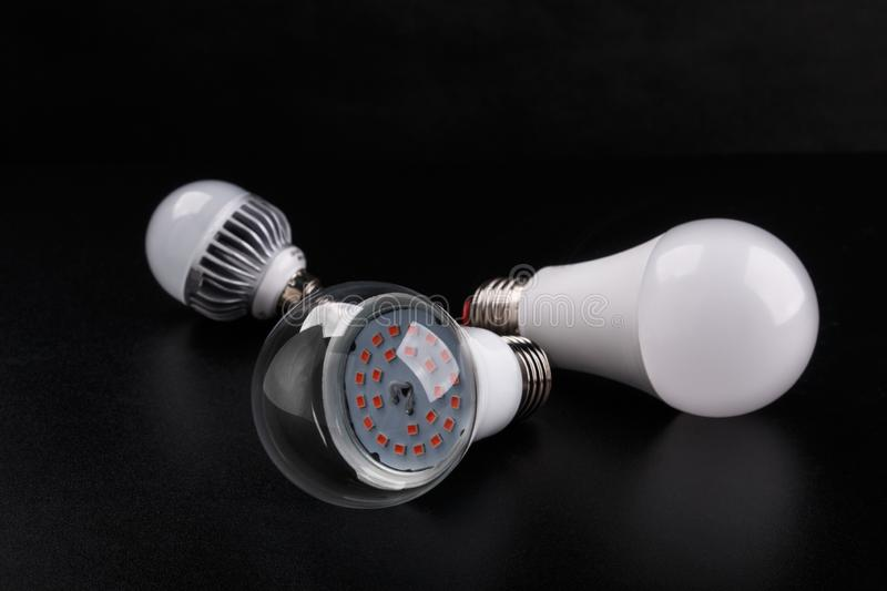 Set with different types of LED bulbs on black background stock photography