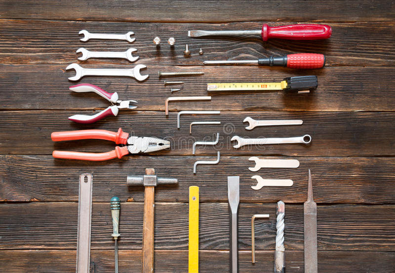 Set of different work tools over dark wooden background. royalty free stock photography