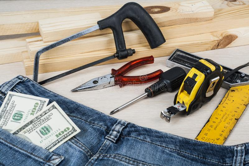 Construction and business concept .Different working tools, dollars in the pocket of jeans on wooden background. royalty free stock images