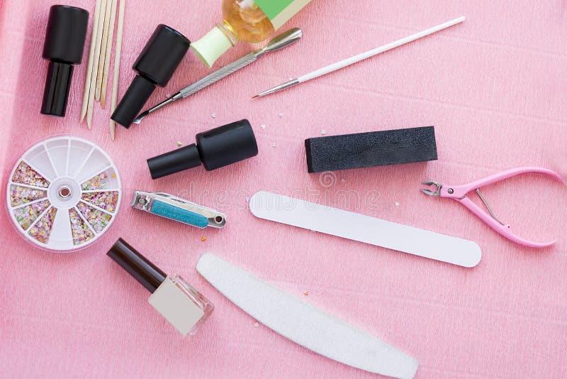Set dla gel manicure'u procedury Butelki gwoździ połysk, drewniani kije, pincety i kartoteka na różowym tle, zdjęcia stock