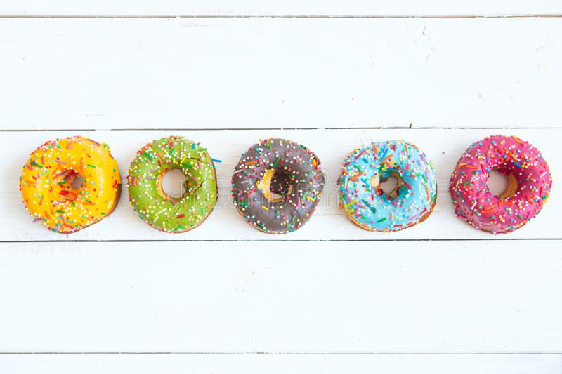Set of donuts on white wooden background.  royalty free stock images