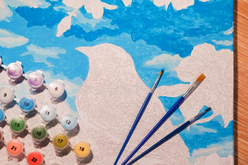 Set for drawing: canvas with numbers, jars of acrylic paint, brushes. The image of a bird. Horizontal photo stock photo