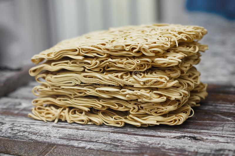 Set of dry raw eggs noodles on wooden food stand. Instant noodles ready to cook. royalty free stock images