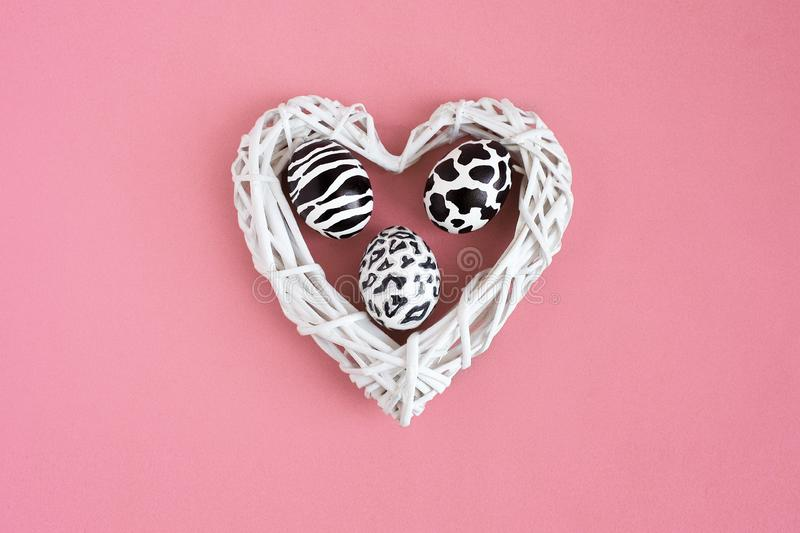 Set of easter eggs painted like zebra, cow, snow leopard inside a white hearton pink background. Top view. royalty free stock photography