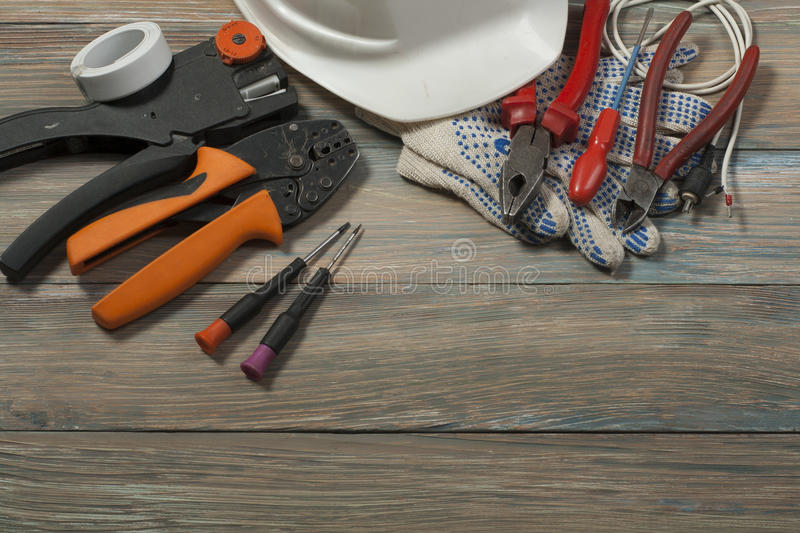Set of electrical tool on wooden background. Accessories for engineering work, energy concept. royalty free stock photography