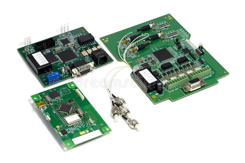 Set of electronic printed circuit boards with optic connectors attached and other components, angled view, isolated on white stock photo