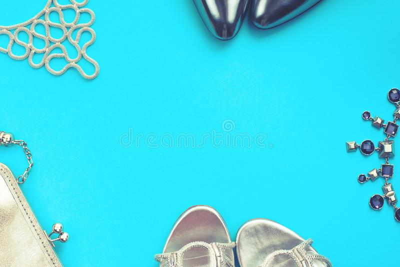 Set of fashion accessories flat lay shoes handbag necklace jewelry silver color on blue background Top view copy space royalty free stock photo