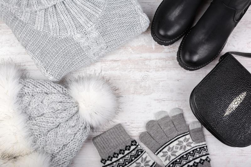A set of fashionable winter women`s clothing. Wool sweater, shoes, handbag, fur hat and gloves on white background stock photo