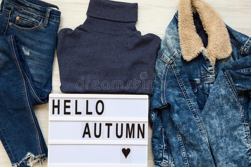 Set of female autumn clothes, modern board with text `Hello autumn`. Top view, from above. Flat lay stock photos