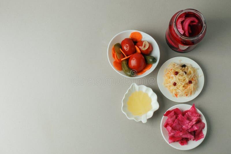 Set fermentujący karmowy wielki dla żyłek zdrowie - odgórny widok szklani puchary i talerz na szarym tle: sauerkraut, kiszona kap zdjęcia royalty free