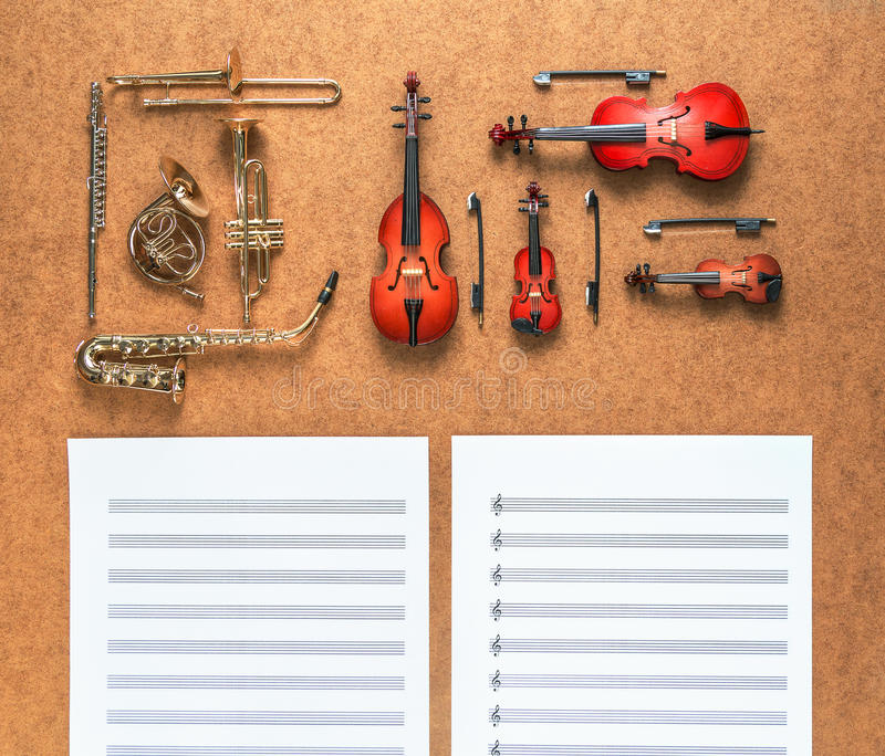 Set of five golden brass wind and four string musical orchestra instruments and sheet music lying near it. Music concept. Set of five golden brass wind and four royalty free stock photos