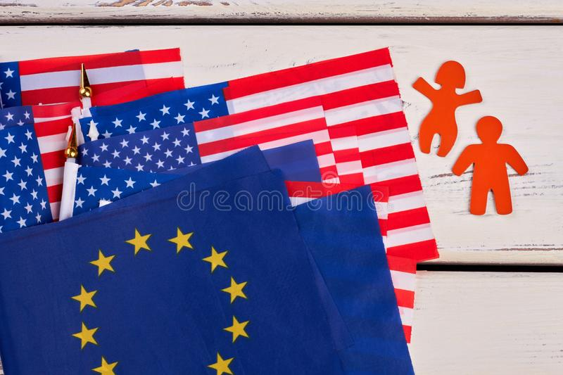 Set of flags, man and woman paper silhouettes. Collection of American flags and flags of europe on vintage wooden surface. People and State royalty free stock images