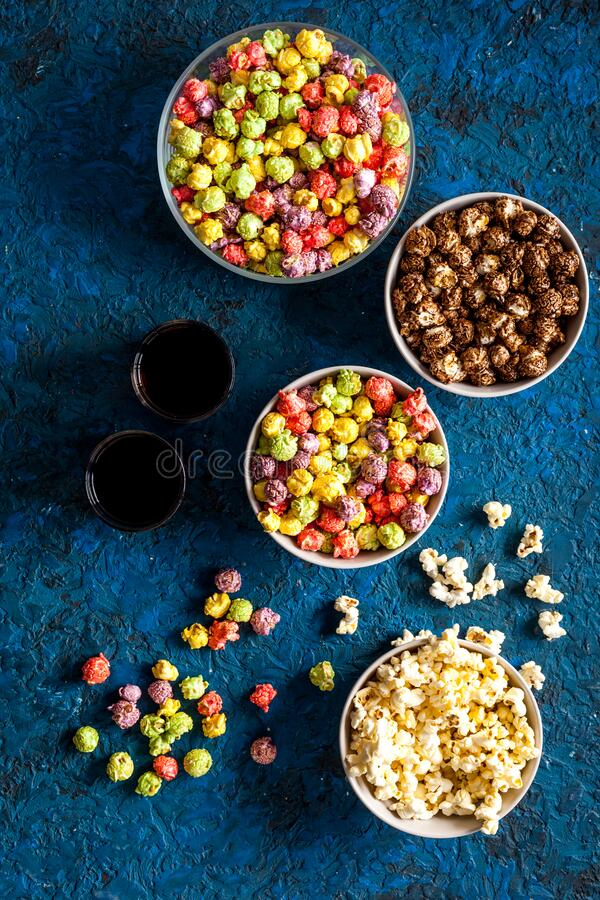 Set of flavored popcorn and soda on blue desk from above stock photos