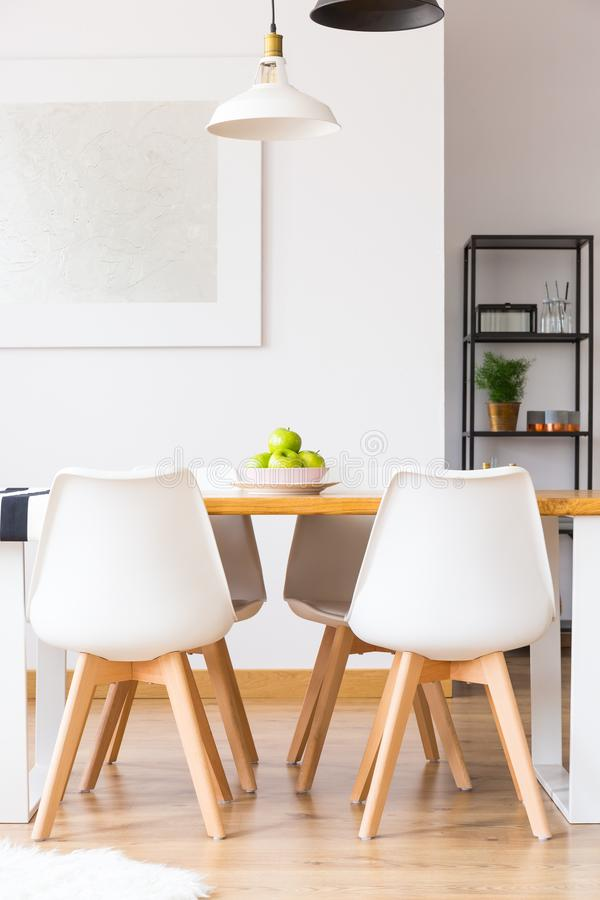 Set of four chairs. Set of four modern chairs standing by a long table with a bowl of apples in a dining room interior royalty free stock images