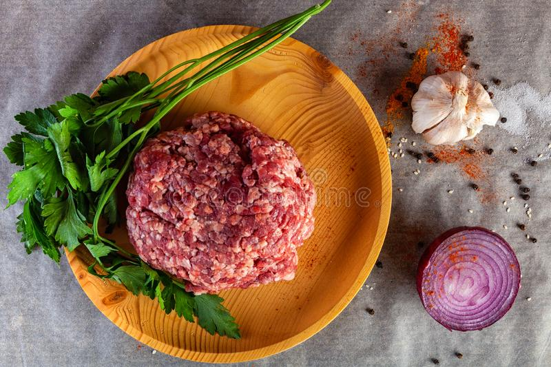 A set of fresh ingredients for cooking ground beef. Flat lay. A set of fresh ingredients for cooking ground beef:beef meat, onion, garlic, tomato, spices, salt royalty free stock image