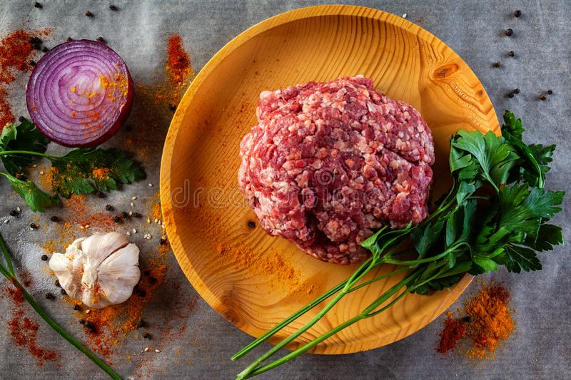 A set of fresh ingredients for cooking ground beef. Flat lay. A set of fresh ingredients for cooking ground beef:beef meat, onion, garlic, tomato, spices, salt stock photos