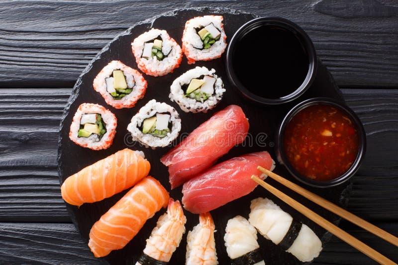 Set of fresh maki, uramaki and nigiri sushi, served on black plate. horizontal top view stock photos