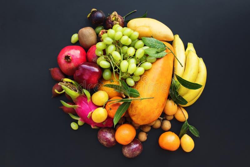 Set fresh organic exotic tropical fruit on dark royalty free stock photos