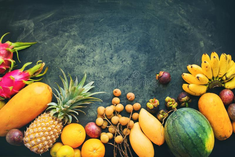 Set fresh organic exotic tropical fruit on dark stock photography