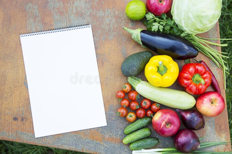 Set of fresh organic vegetables and fruits on rustic wooden table and notebook. Diet plan. Healthy food. Top view. From above. stock images