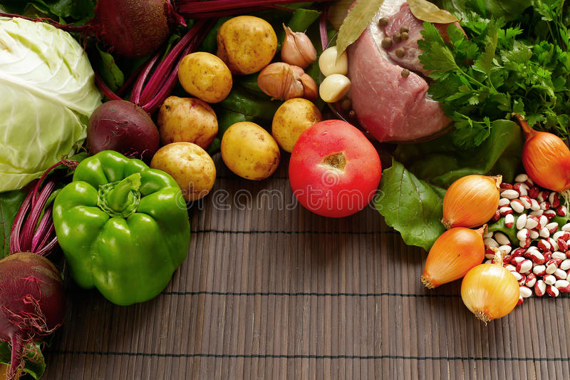 A set of fresh produce on a brown wooden background. A set of vegetables and meat for cooking red borsch royalty free stock photography