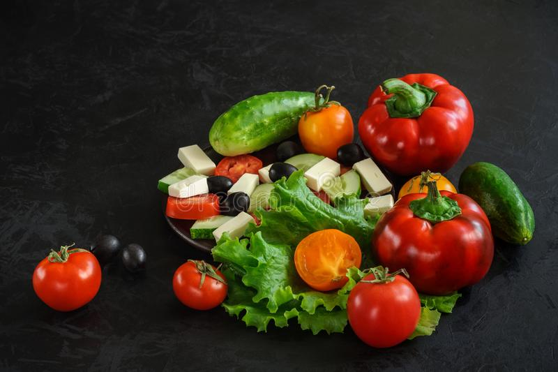 Set of fresh ripe whole and chopped vegetables for cooking Greek salad on a black concrete surface with space for text, stock photo
