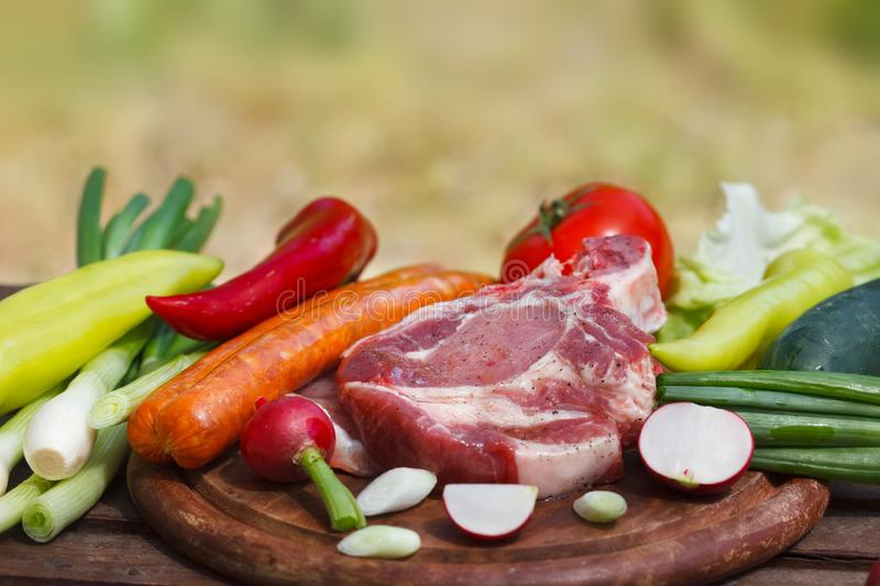 Set of fresh vegetables and raw steak meat on wooden board. Outdoor image, blurred nature in background stock photography