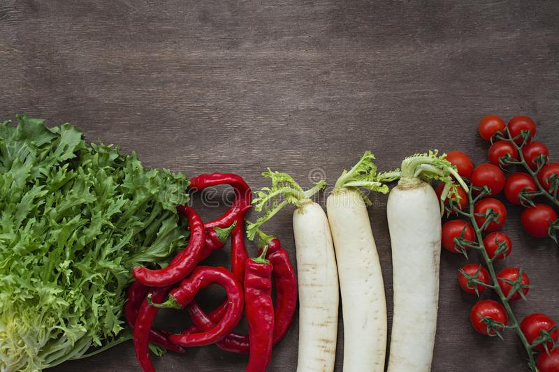 Set of fresh vegetables on a wooden background. Chili pepper, daikon radish, cherry, salad on the table. Place for text stock photo