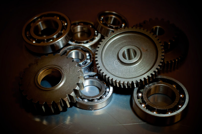 Set of gears and ball-bearings. On a polished steel surface stock image