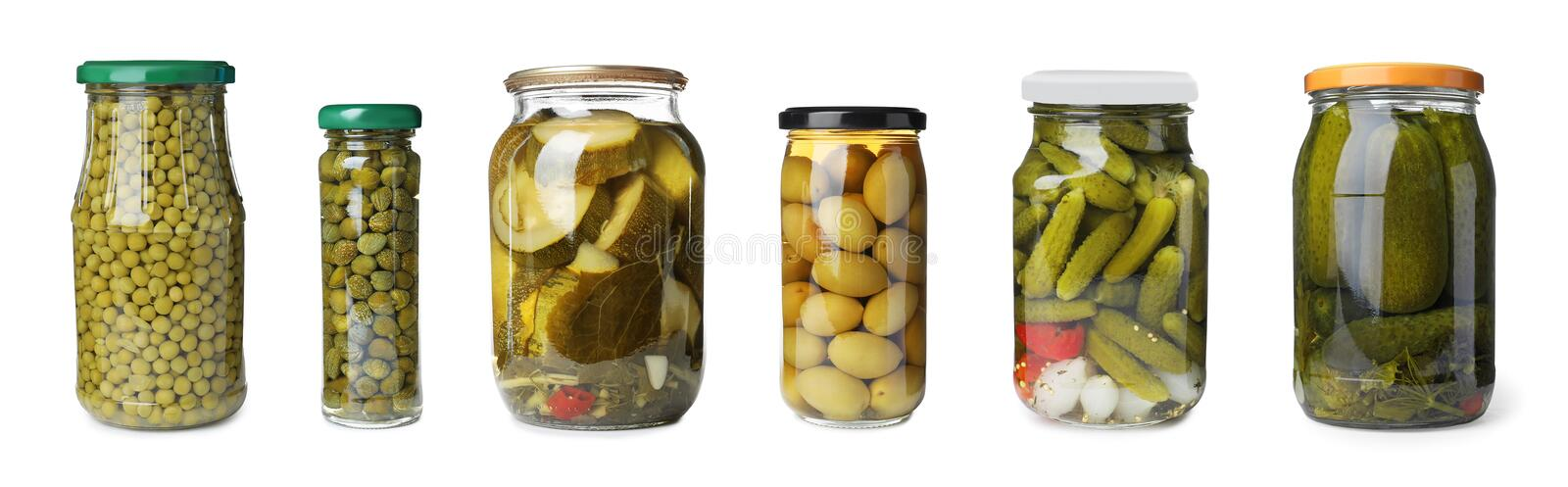 Set of glass jars with different pickled vegetables on background stock image