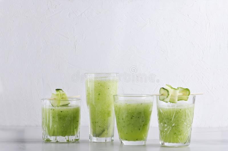Set of glasses of cucumber smoothie on the white table against white wall.Empty space for text royalty free stock photography