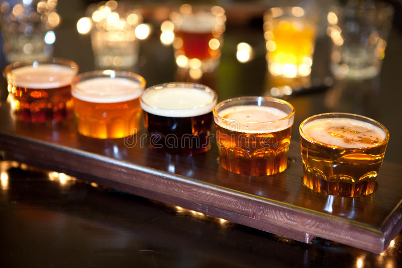 Set of glasses of light and dark beer on a pub background. Set of glasses of different light and dark beer on a pub background stock images