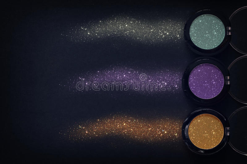 Set of glitter eyeshadow make up and powder sparkle dust. Top view set of glitter eyeshadow make up and powder sparkle dust on black background royalty free stock images