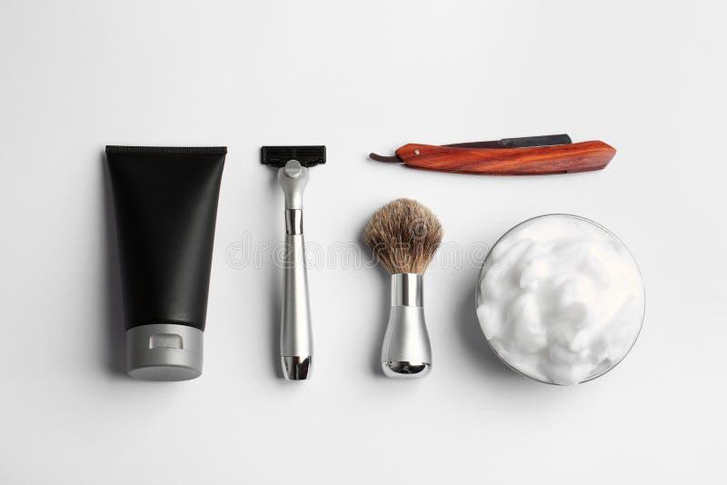 Set golenia wyposa?enie i m??czyzn kosmetyczni produkty na lekkim tle obraz stock