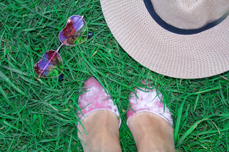 Set on the grass, women`s legs in shoes, glasses in the form of a heart and a hat. royalty free stock photos