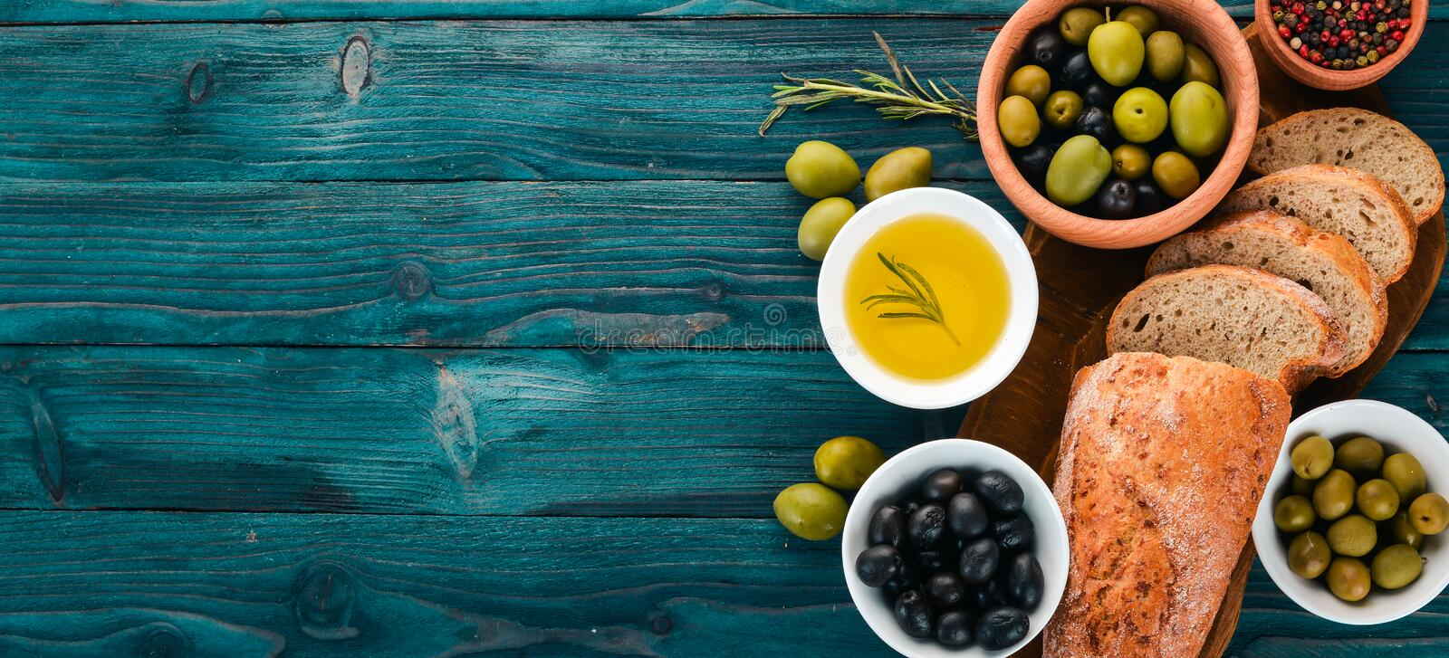 A set of green olives and black olives, and snacks. On a blue wooden table. Free space for text royalty free stock image