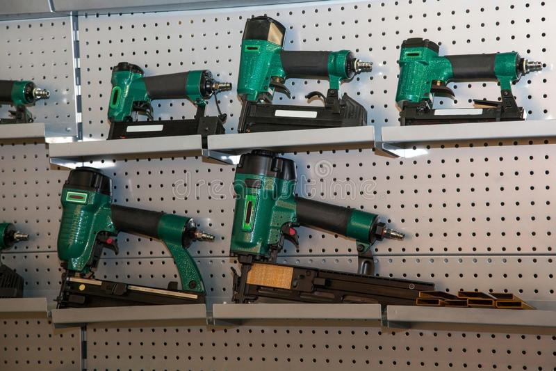 Set of green power drills on metal shelves.  stock photos