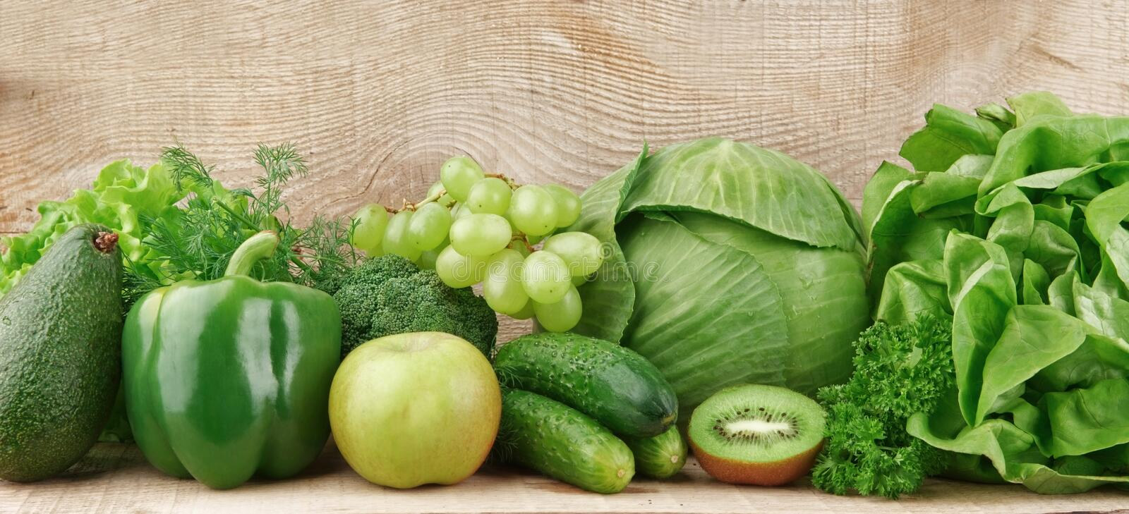 Set of green vegetables and fruits. Group of green vegetables and fruits on wooden background