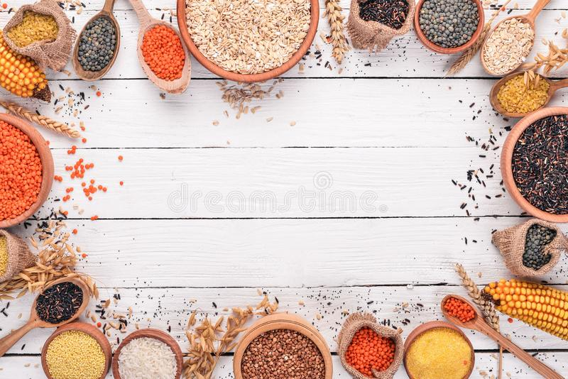 Set of Groats and Grains. Buckwheat, lentils, rice, millet, barley, corn, black rice. On a white wooden background. royalty free stock photo