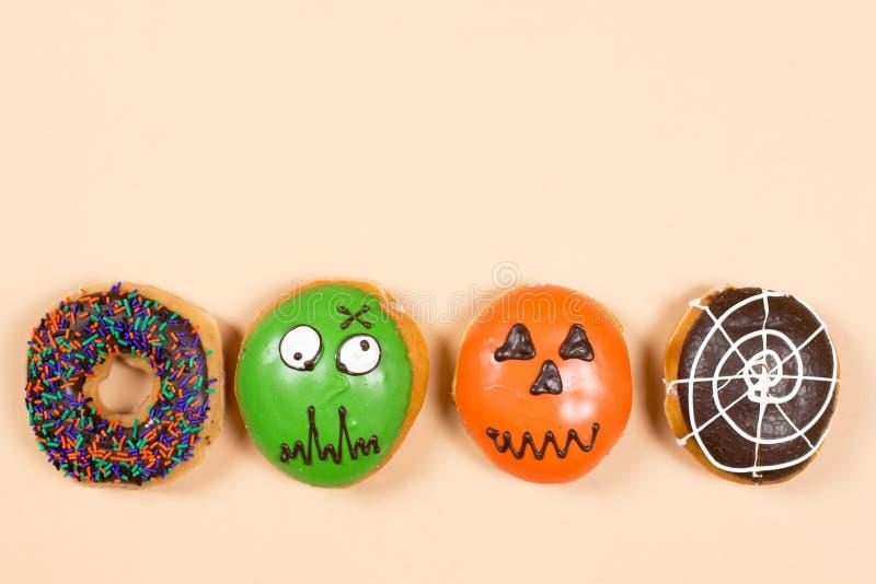 Set of halloween donuts. Halloween sprinkles, green zombie, pumpkin, spider web set of halloween donuts background stock photography