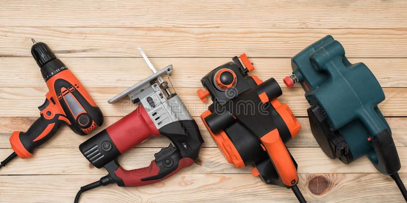 Set of hand carpentry power tools for woodworking lies on a light wooden background. Directly above royalty free stock photo