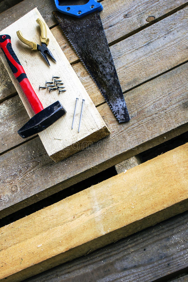 Set of hand tools: hacksaw, pliers, screws, hammer, nails - on a bar and wooden unplaned boards. Hand tools for building royalty free stock photography