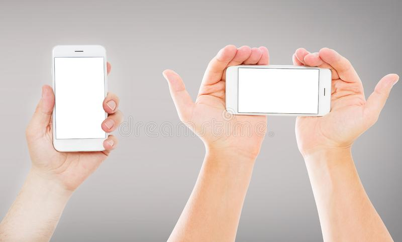 Set hands holding empty blank screen mobile phones  on gray background, vertical and horizontal empty display stock photos