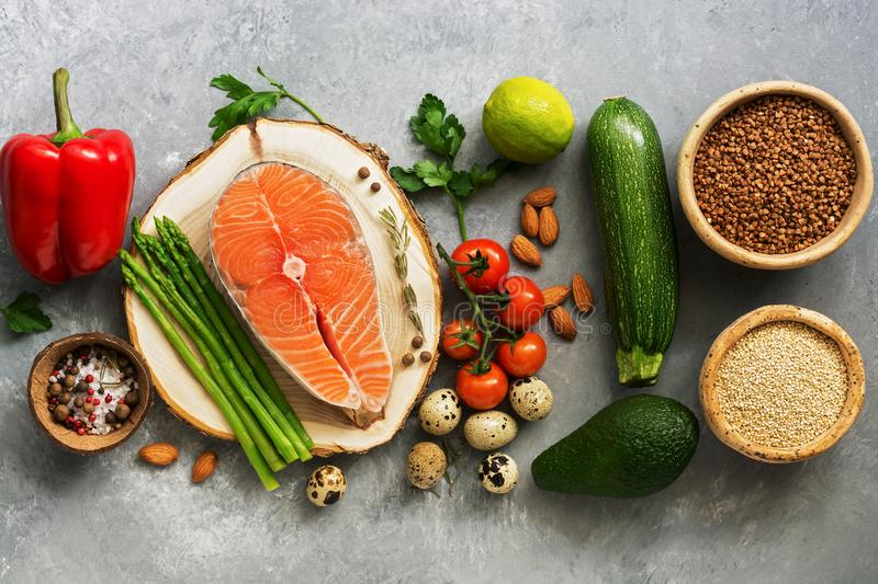 A set of healthy balanced super food, fresh salmon, vegetables, egg, cereals and nuts on a gray background. Top view, flat lay royalty free stock image